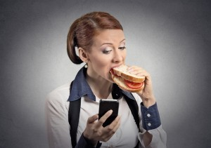 woman reading message on smartphone eating sandwich