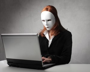 Masked businesswoman using a laptop